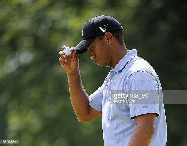 Tiger Woods of the US tips his cap after sinking a birdie putt on the second hole during the first round at the 91st PGA Championship at the...