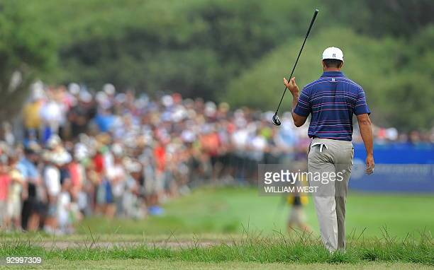 Tiger Woods of the US twirls his club as he walks down the fairway during the first round of the Australian Masters golf tournament at the Kingston...
