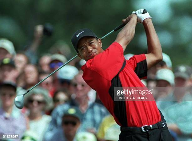 Tiger Woods of the US watches his tee shot off the first tee 13 April during the final round of the Masters tournament at Augusta National Golf Club...