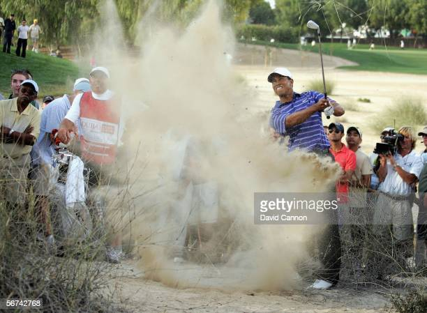 Tiger Woods of the USA blasts from some desert scrub for his second shot at the par 4 17th hole during the third round of the 2006 Dubai Desert...