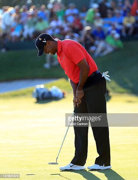Tiger Woods of the USA closes his eyes as he taps in his par putt at the par 4 18th hole to secure his victory during the final round of the 2012...