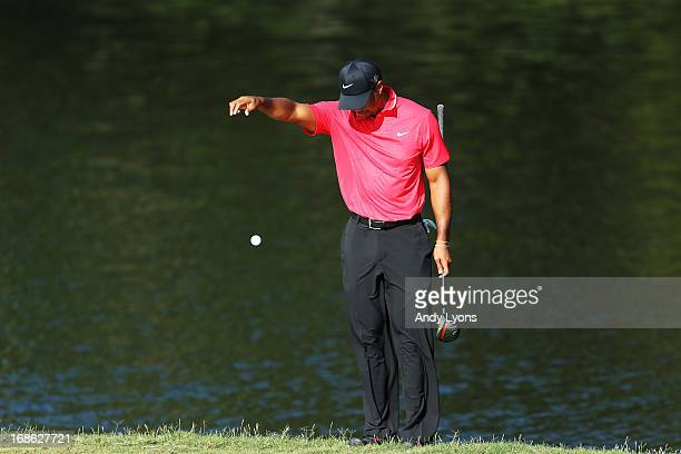 Tiger Woods of the USA drops a ball on the 14th hole after hitting into the water hazard during the final round of THE PLAYERS Championship at THE...