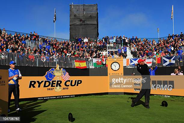 Tiger Woods of the USA hits his tee shot on the first hole as Francesco Molinari of Europe looks on in the singles matches during the 2010 Ryder Cup...
