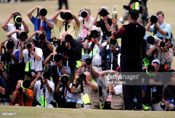 Tiger Woods of the USA holds the Claret Jug aloft to an army of photographers after securing a five shot victory at the 134th Open Championship at...