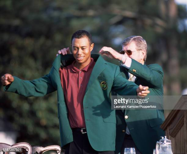 Tiger Woods of the USA is presented with his Green Jacket by the Tournament chairman Hootie Johnson after Woods' 3rd victory in the US Masters Golf...
