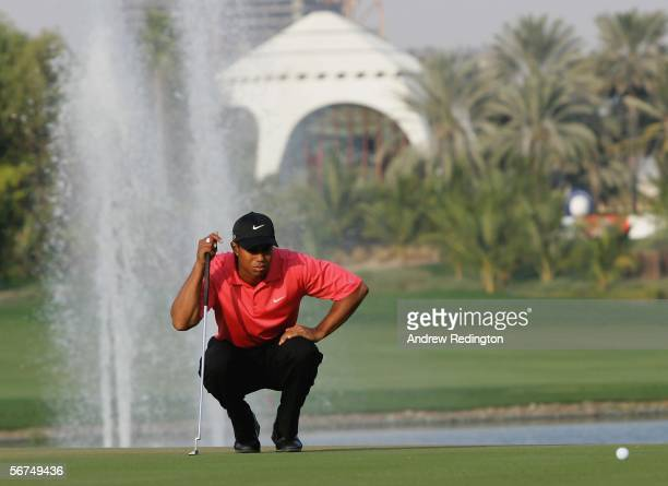 Tiger Woods of the USA lines up his birdie putt on the 18th green during the final round of the Dubai Desert Classic on the Majilis Course at...