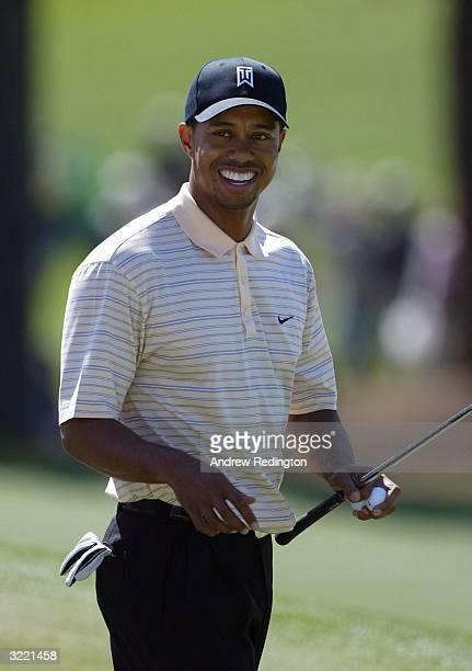 Tiger Woods of the USA looks on as he smiles on the seventh hole during the first practice day for the Masters at the Augusta National Golf Club on...