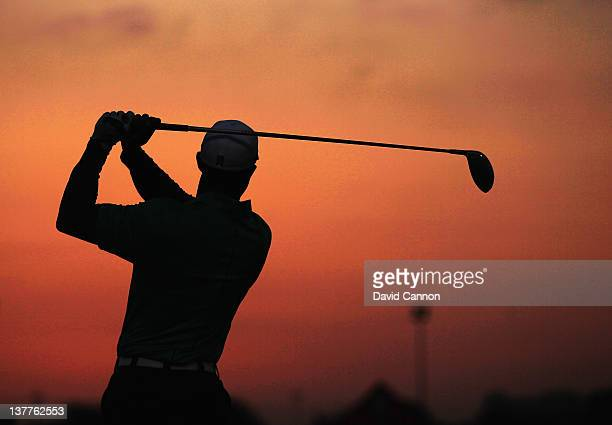Tiger Woods of the USA on the driving range as the sun rises in the desert before teeing off in the first round of the Abu Dhabi HSBC Championship at...