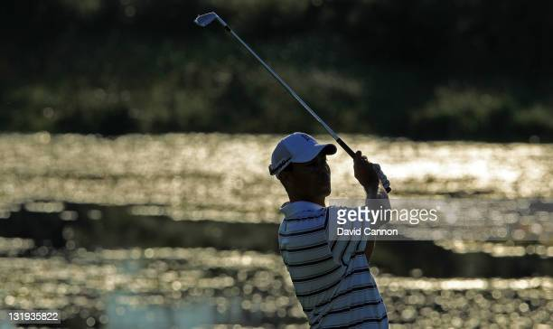 Tiger Woods of the USA plays his second shot at the 1st hole as the early morning sun shines off the lake ahead of the 2011 Emirates Australian open...