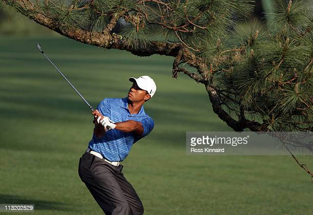 Tiger Woods of the USA plays his second shot on the 17th hole from under The Eisenhower Tree during the third round of the 2011 Masters Tournament at...