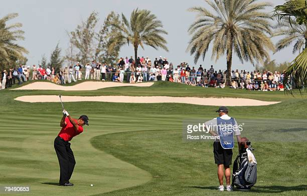Tiger Woods of the USA plays his second shot on the par four 1st hole during the final round of the Dubai Desert Classic on the Majlis Course held at...