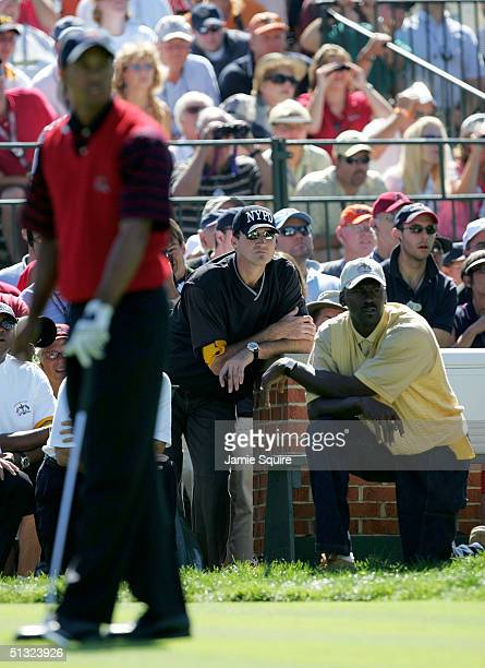 Tiger Woods of the USA plays off the third tee as former NBA star Michael Jordan and NHL star Mario Lemieux watch during his match against Paul Casey...