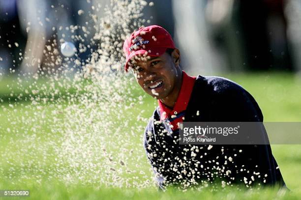 Tiger Woods of the USA plays out from a bunker on the third green during his four-ball match against European team players Darren Clarke and Ian...