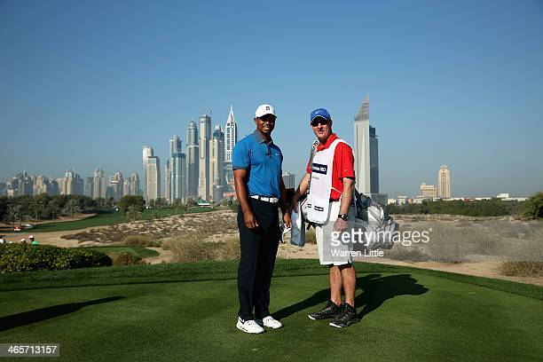 Tiger Woods of the USA poses with his caddie Joe LaCava on the eighth tee during the proam as a preview for the 2014 Omega Dersert Classic on the...