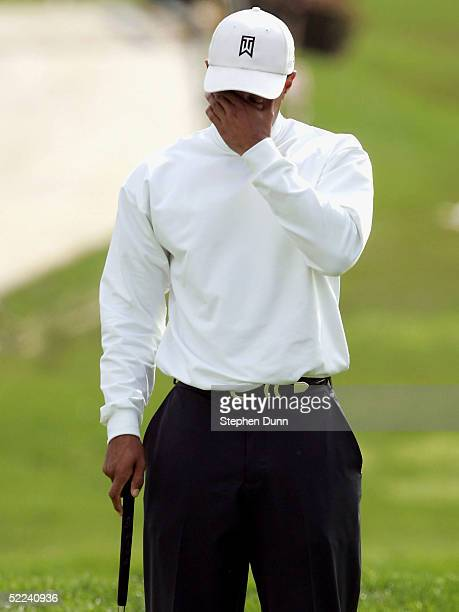 Tiger Woods of the USA reacts after missing a birdie putt attempt on the ninth hole in his match with Nick O'Hearn of Australia during the second...
