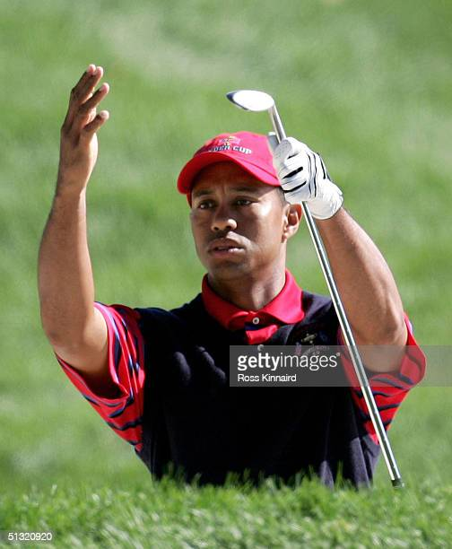 Tiger Woods of the USA reacts after playing out from a bunker 9th hole during his four-ball match against European team players Darren Clarke and Ian...