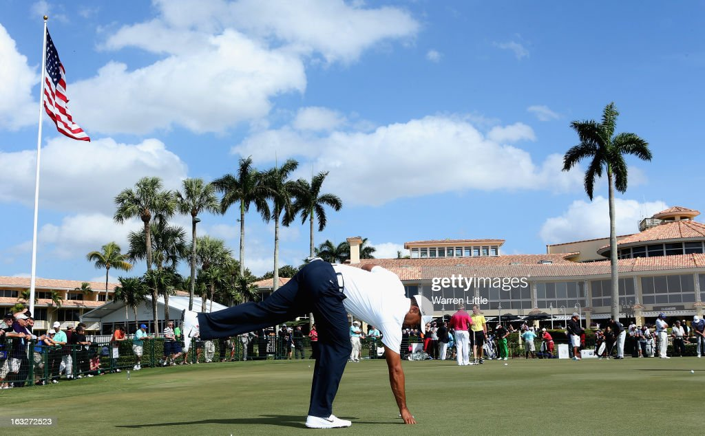 Tiger Woods of the USA retrieves his ball from the hole on the practice putting green ahead of the WGC - Cadillac Championship at the Doral Golf Resort & Spa on March 6, 2013 in Miami, Florida.