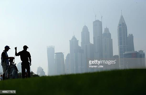 Tiger Woods of the USA selects a club on the 13th green during the second round of the 2014 Omega Dubai Desert Classic on the Majlis Course at the...