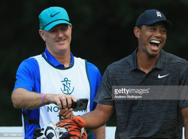 Tiger Woods of the USA shares a joke with his caddie Joe LaCava during the Pro Am event prior to the start of The Northern Trust at Ridgewood CC on...