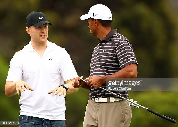 Tiger Woods of the USA talks with Geelong Cats footballer Gary Ablett during the ProAm ahead of the Australian Masters at The Victoria Golf Club on...