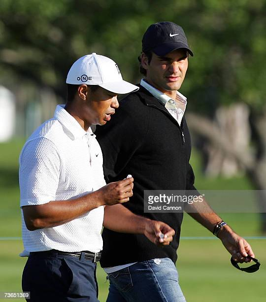 Tiger Woods of the USA walks to his second shot to the 11th hole watched by world tennis no 1 Roger Federer of Switzerland who walked with Tiger for...