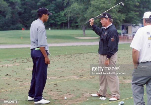 Tiger Woods of the USA with his golf coach Butch Harmon during a practice session in Milwaukee Wisconsin circa 1996