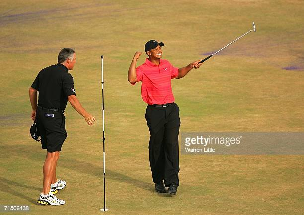 Tiger Woods of USA celebrates victory on the 18th green as his caddy Steve Williams looks on at the end of the final round of The Open Championship...