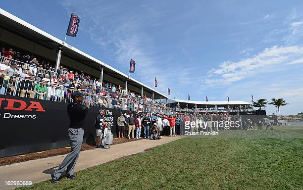 Tiger Woods of USA plays his approach shot after he put his second shot into the grandstand on the 18th hole during the third round of the Honda...