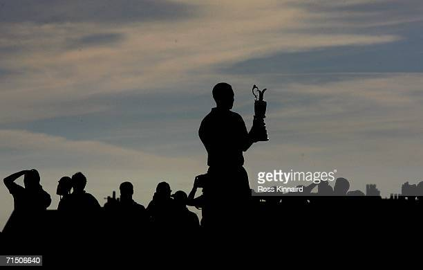 Tiger Woods of USA stands with the claret jug following his two shot victory at the end of the final round of The Open Championship at Royal...