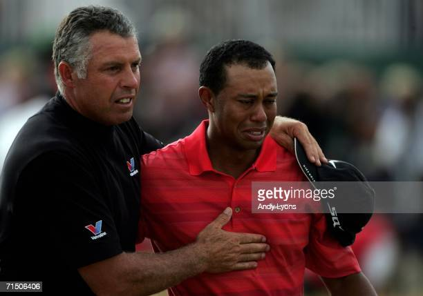 Tiger Woods of USA walks off the 18th green in tears with his caddy Steve Williams following his victory at the end of the final round of The Open...