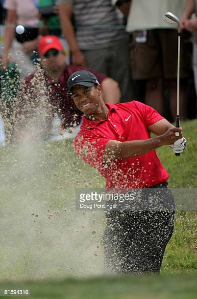 Tiger Woods pitches out of a sandtrap as he takes his third shot on the ninth hole during the playoff round of the 108th US Open at the Torrey Pines...