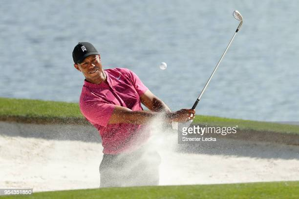 Tiger Woods plays a shot from a bunker on the 14th hole during the first round of the 2018 Wells Fargo Championship at Quail Hollow Club on May 3,...
