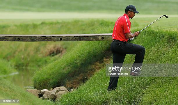 Tiger Woods plays a shot from creekside on the 11th hole during the final round of the Memorial Tournament presented by Nationwide Insurance at...