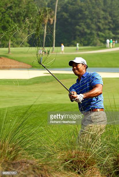 Tiger Woods plays a shot from the rough on the 12th hole during the first round of THE PLAYERS Championship held at THE PLAYERS Stadium course at TPC...