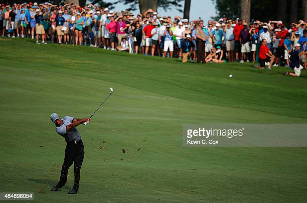 Tiger Woods plays his second shot on the 18th hole during the third round of the Wyndham Championship at Sedgefield Country Club on August 22, 2015...