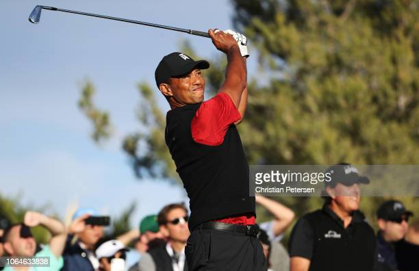 Tiger Woods plays his shot from the 13th tee as Phil Mickelson looks on during The Match Tiger vs Phil at Shadow Creek Golf Course on November 23...