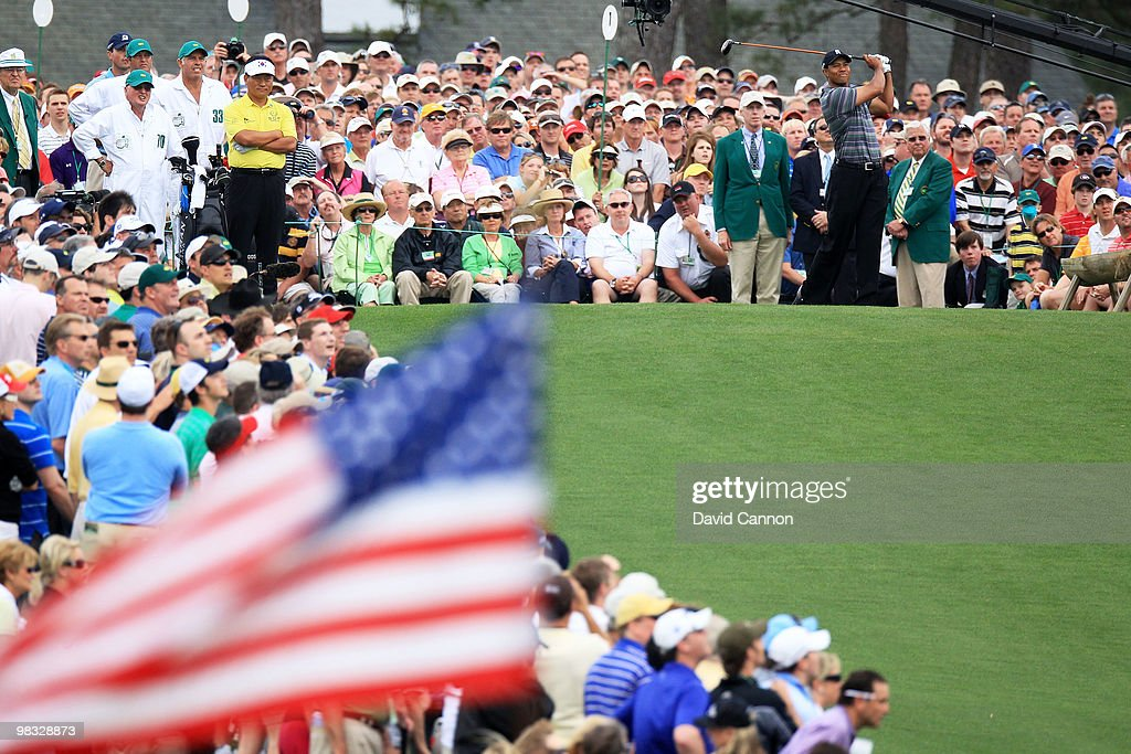 Tiger Woods (R) plays his tee shot on the first hole as K.J. Choi of Korea (L) and a gallery of fans look on during the first round of the 2010 Masters Tournament at Augusta National Golf Club on April 8, 2010 in Augusta, Georgia.