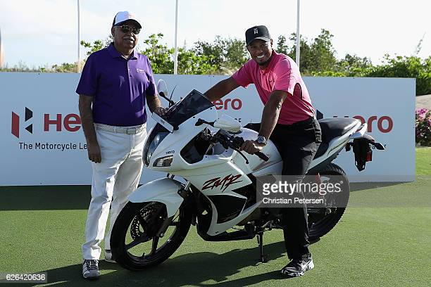 Tiger Woods poses alongside Pawan Munja of Hero Motocycles for photographs ahead of the Hero World Challenge at Albany The Bahamas on November 29...
