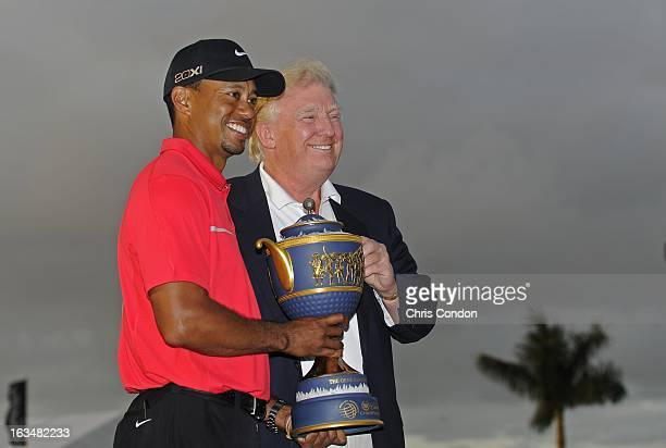 Tiger Woods poses with the Gene Sarazen Cup and Donald Trump after winning the World Golf ChampionshipsCadillac Championship at TPC Blue Monster at...