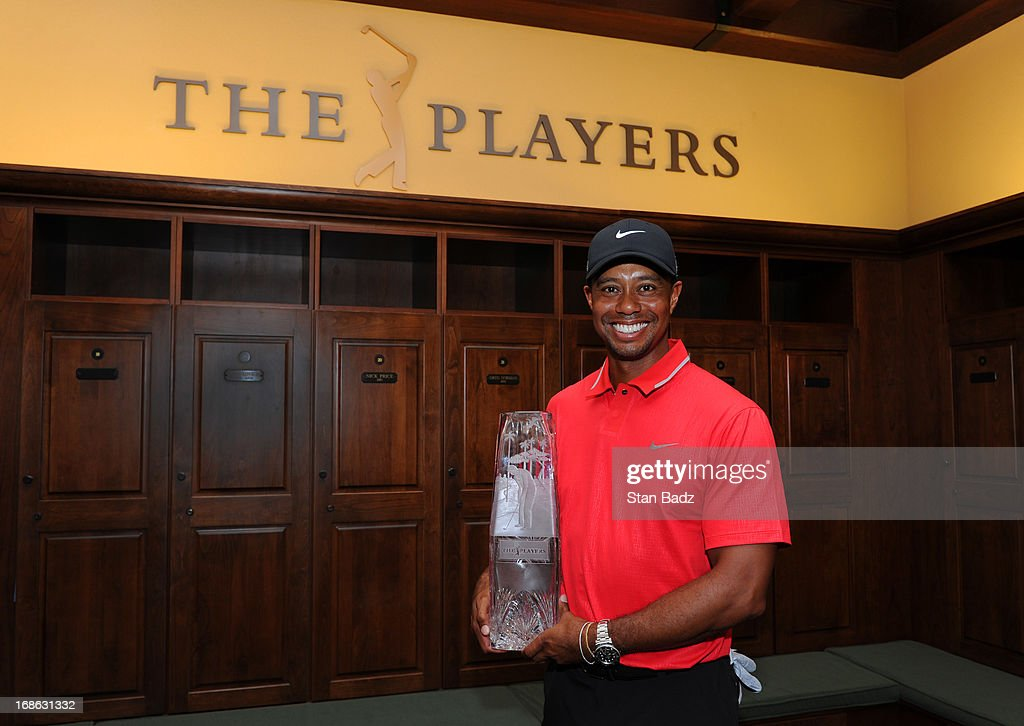 Tiger Woods poses with the winner's trophy in the champions locker room after the final round of THE PLAYERS Championship on THE PLAYERS Stadium Course at TPC Sawgrass on May 12, 2013 in Ponte Vedra Beach, Florida.