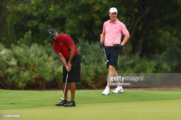 Tiger Woods putts on the first green as former NFL player Peyton Manning looks on during The Match: Champions For Charity at Medalist Golf Club on...