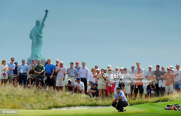 Tiger Woods putts on the second green during first round play at the Barclays Golf Tournament at Liberty National in Jersey City NJ Statue of Liberty...