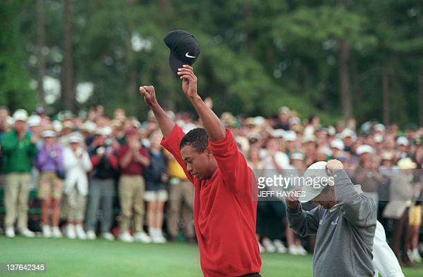 Tiger Woods raises his arms in victory after winning the 1997 Masters tournament 13 April 1997 at Augusta National Golf Club in Georgia Woods won the...
