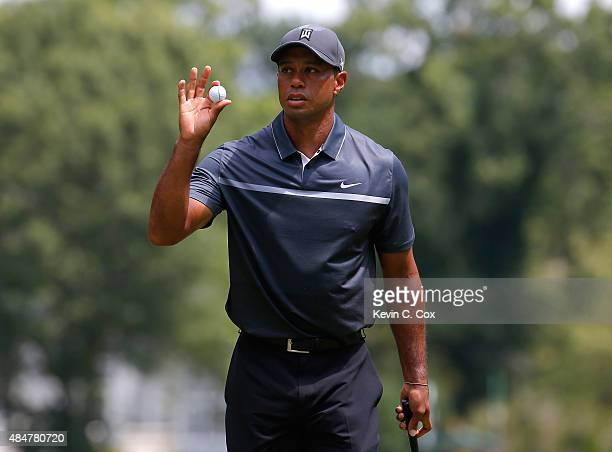 Tiger Woods reacts after a birdie putt on the third green during the second round of the Wyndham Championship at Sedgefield Country Club on August...