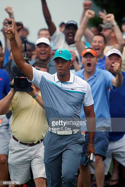 Tiger Woods reacts after chipping in for birdie on the 10st hole during the first round of the Wyndham Championship at Sedgefield Country Club on...