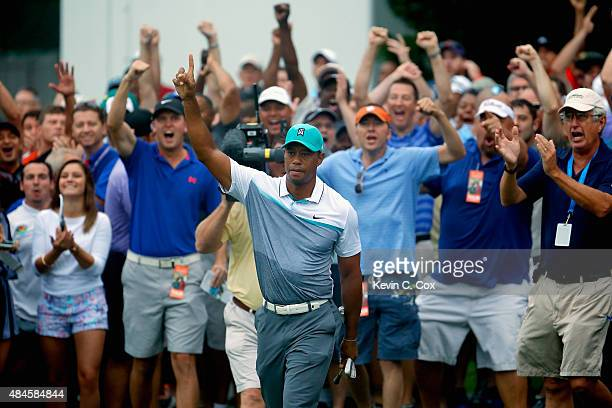 Tiger Woods reacts after chipping in for birdie on the 10th hole during the first round of the Wyndham Championship at Sedgefield Country Club on...