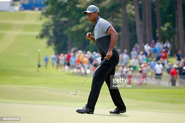 Tiger Woods reacts after making his par putt on the 10th hole during the third round of the Wyndham Championship at Sedgefield Country Club on August...