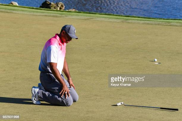 Tiger Woods reacts and drops his putter on the 18th hole green after missing a birdie putt during the second round of the Arnold Palmer Invitational...