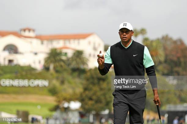 Tiger Woods reacts to a made putt on the 10th hole green during the continuation of the first round of the Genesis Open at Riviera Country Club on...