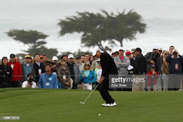 Tiger Woods reacts to a missed putt on the fifth hole as a gallery of fans looks on during the second round of the ATT Pebble Beach National ProAm at...